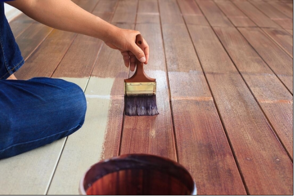 Picture of working applying deck stain to a new deck.