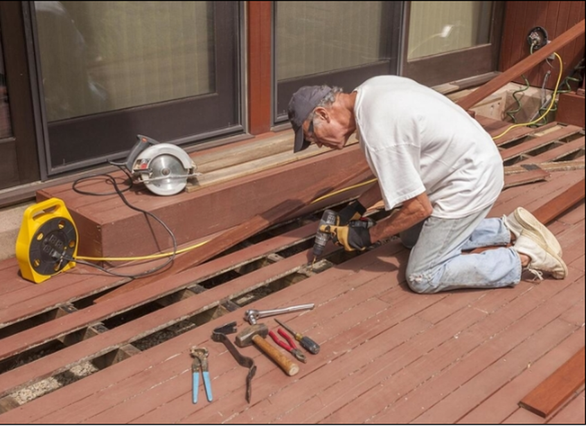 Picture of a worker refurbising a deck